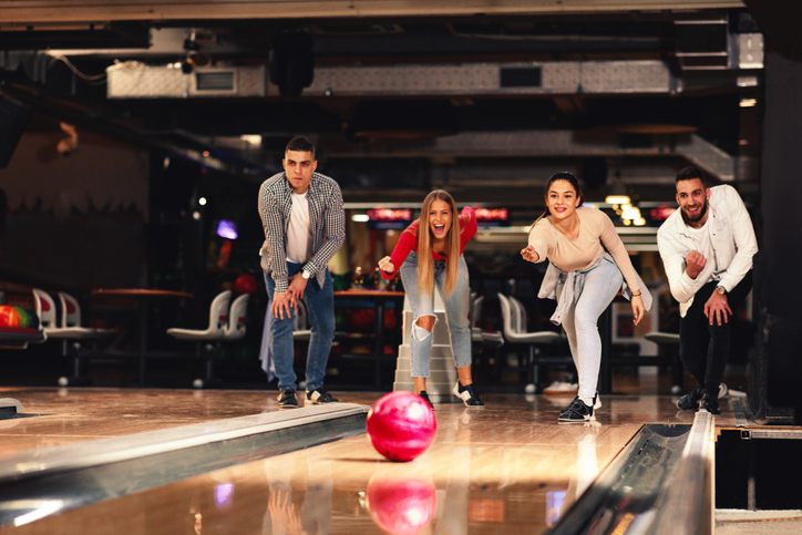 A group of friends cheer on a bowler