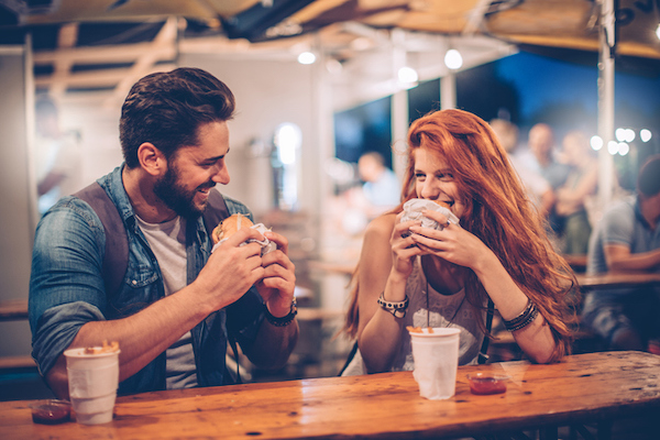 A couple enjoy a burger on a patio