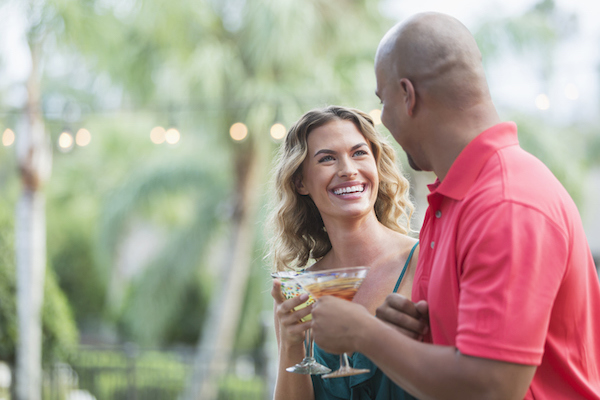 A couple cheers in an outdoor setting